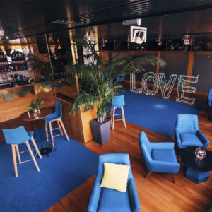 Function room with stylish blue decor with matching blue chairs and tables and large signage saying Love