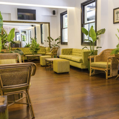 Green sofas in function room with foot stools