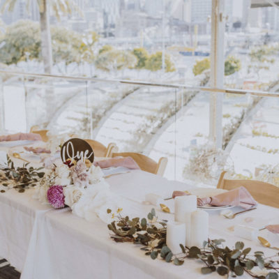 White table overlooking city set for a wedding with flowers