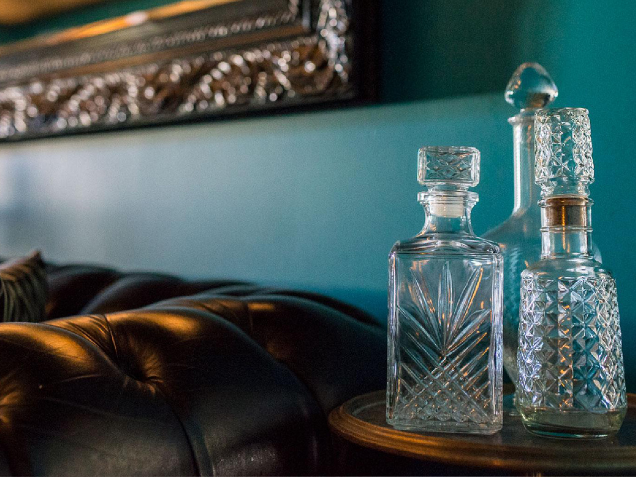 Liquor bottles in foreground next to leather sofa and blue walled room