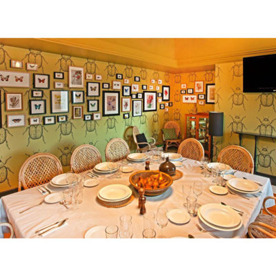 Square white table set for a dining experience with framed butterfly pictures on wall