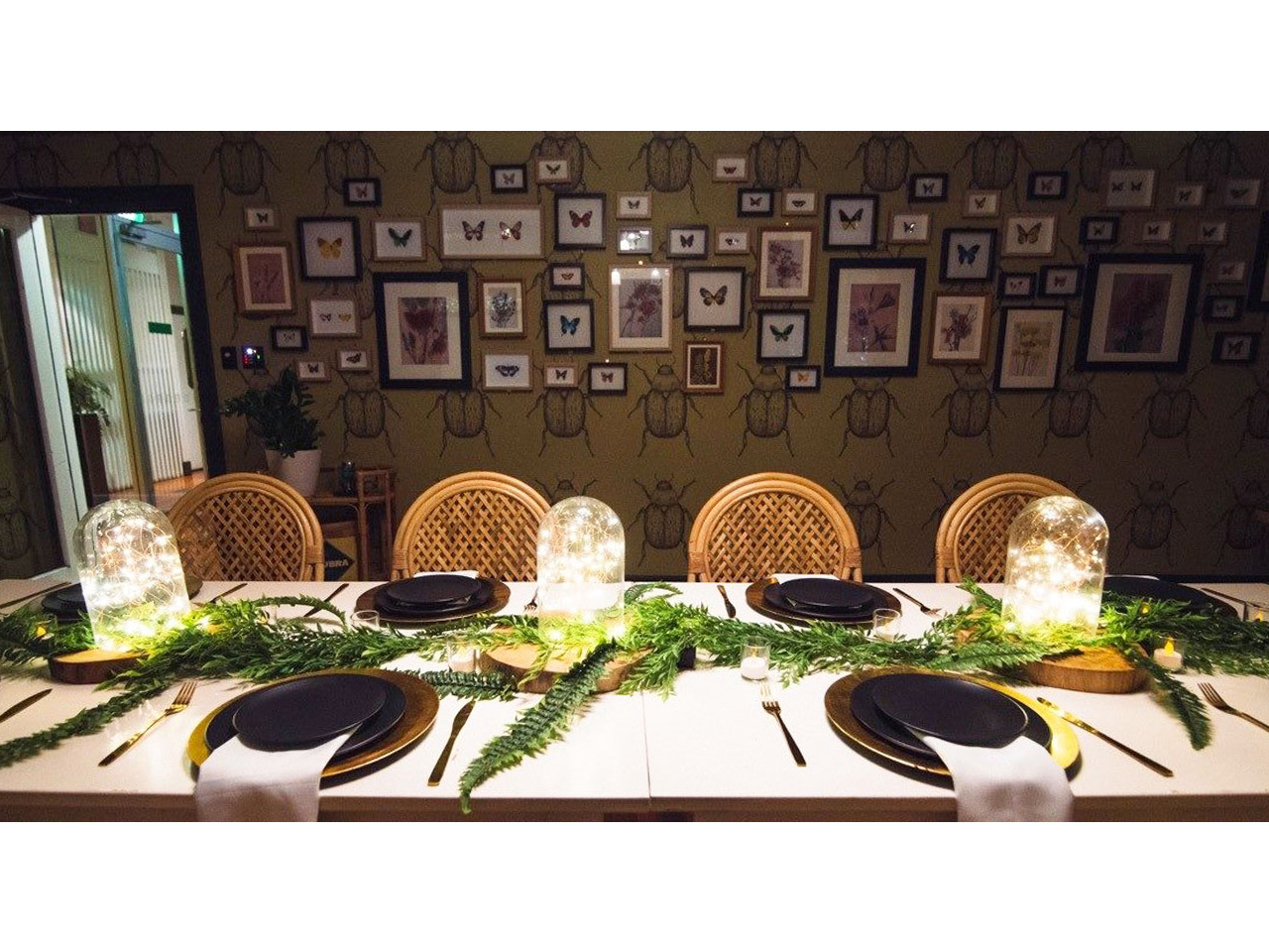 Long table set for a dining experience with framed butterfly pictures on wall