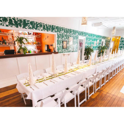 Long white table set for an event with bar in background