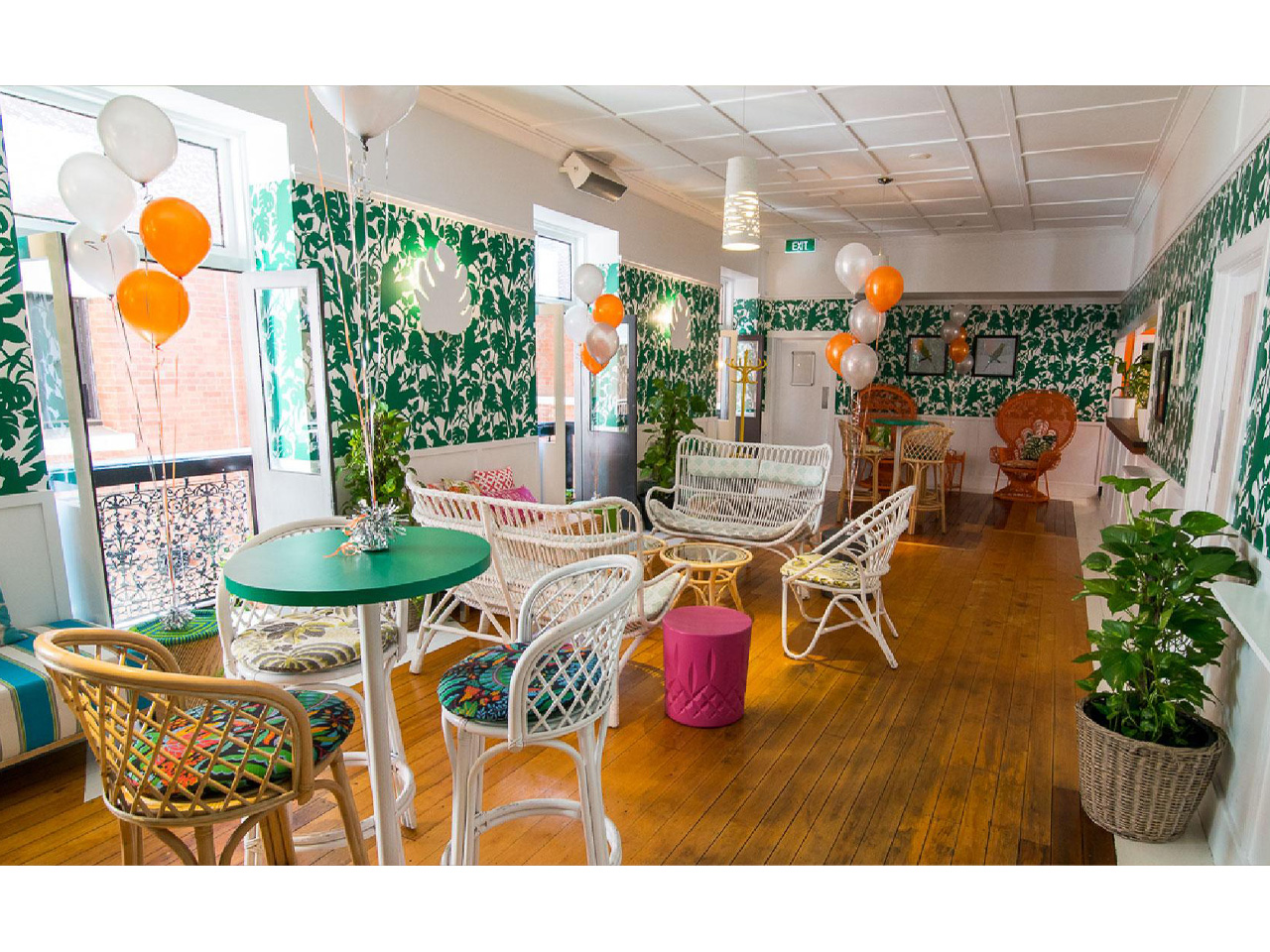 Brightly lit event space with wicker round green tables and white chairs