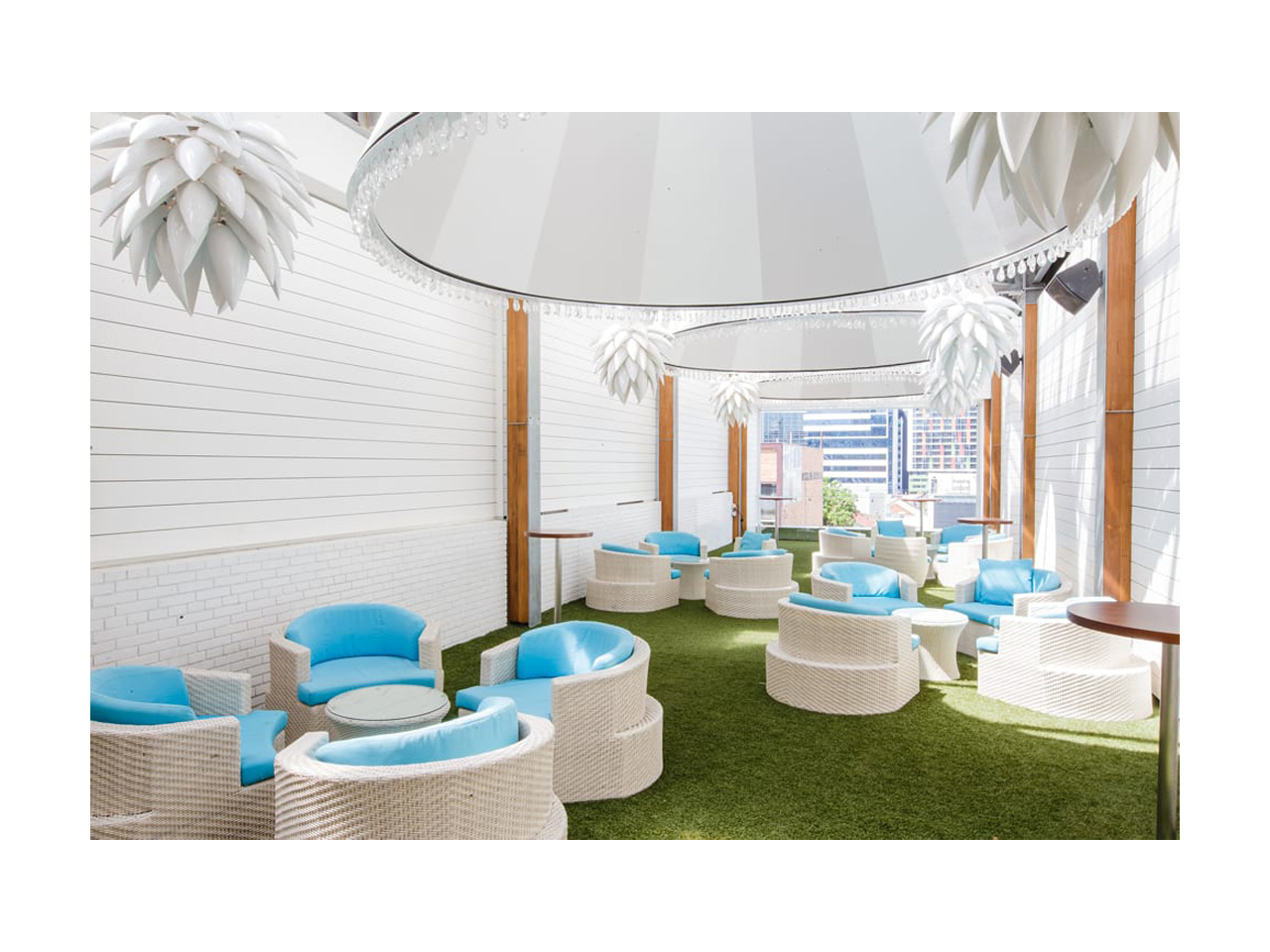 Semi-outdoor function room with white decor and blue and white individual seating with round tables