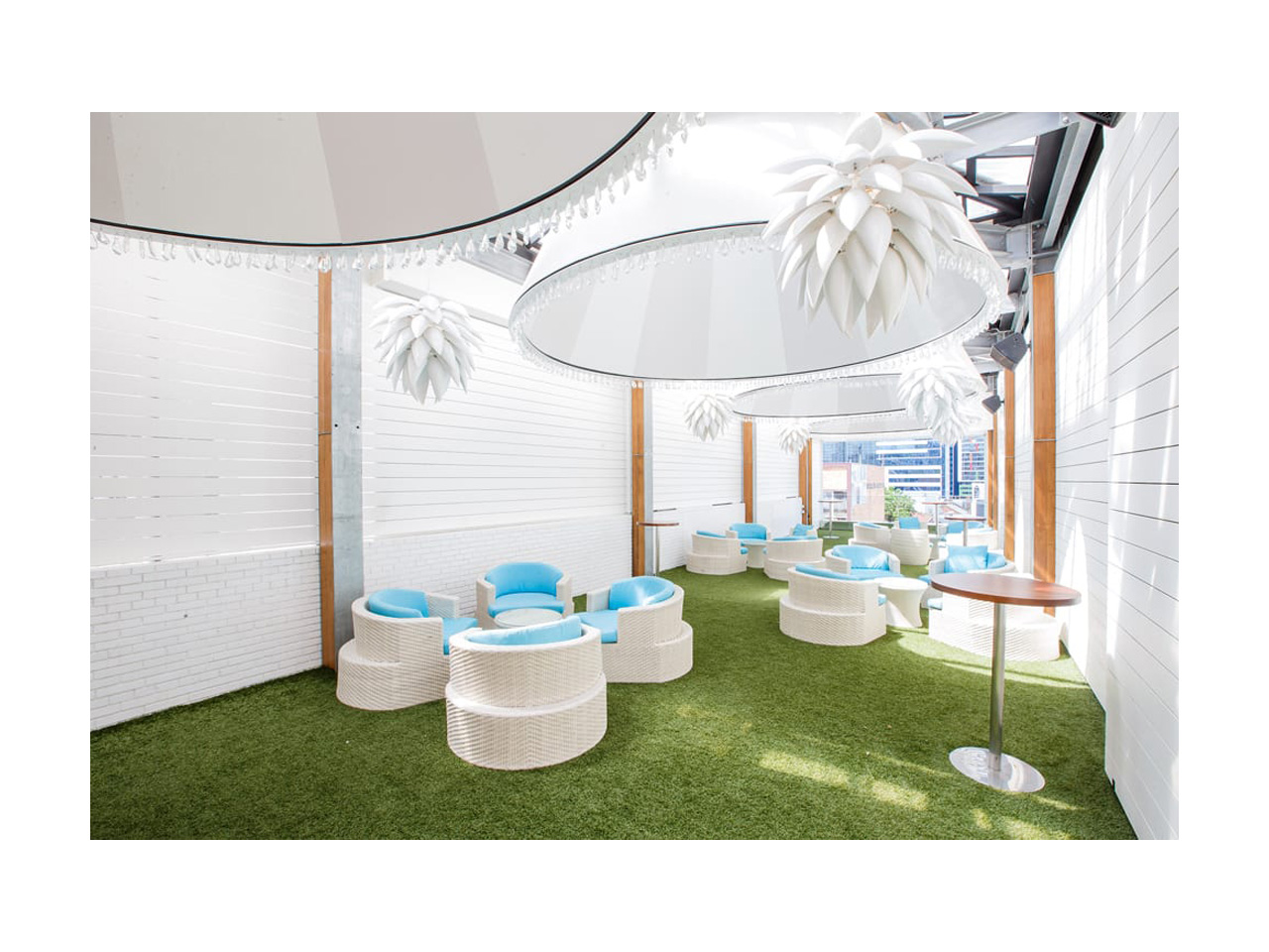 Semi-outdoor function room with white decor and blue and white individual seating with round tables and large overhead lighting