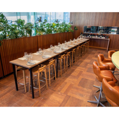 Long table in event venue set for dinner and drinks