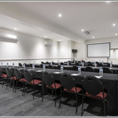 Large conference room with rows of seats and black tables with projector screen