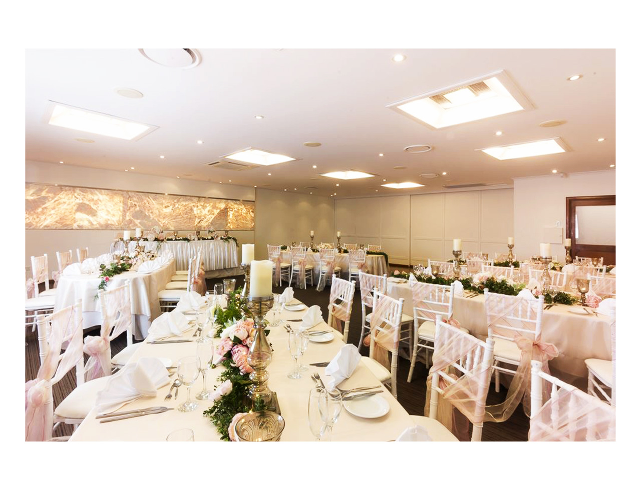 Room set for wedding reception with white tables and chairs