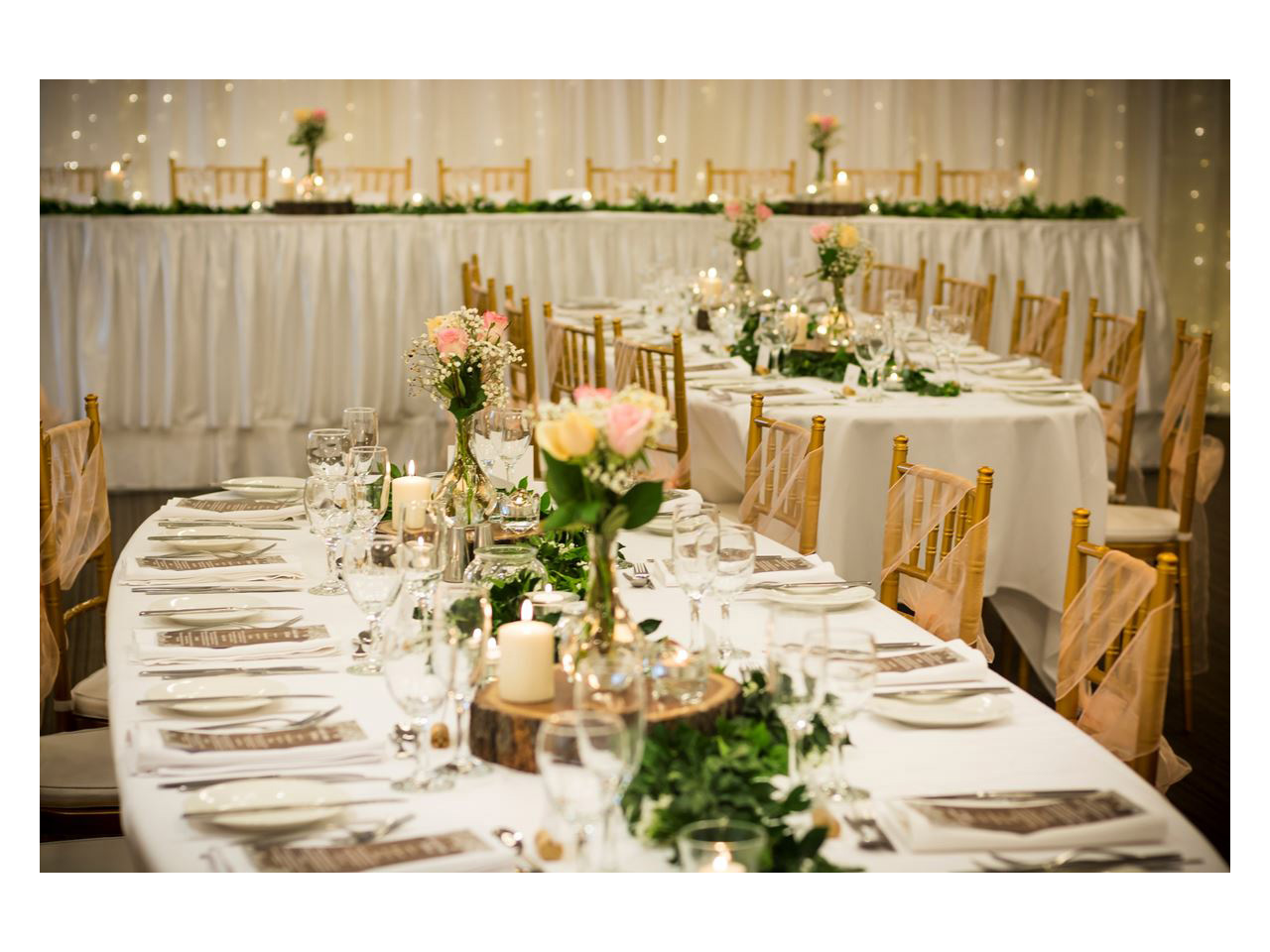 Room set for wedding reception with white and pink tables and wooden chairs