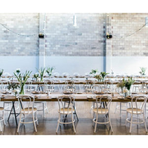 Wedding venue with long tables decorated for wedding with overhead light bulbs