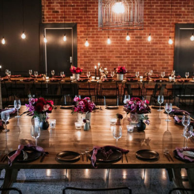 Large venue for events with long table and overhead bulbs
