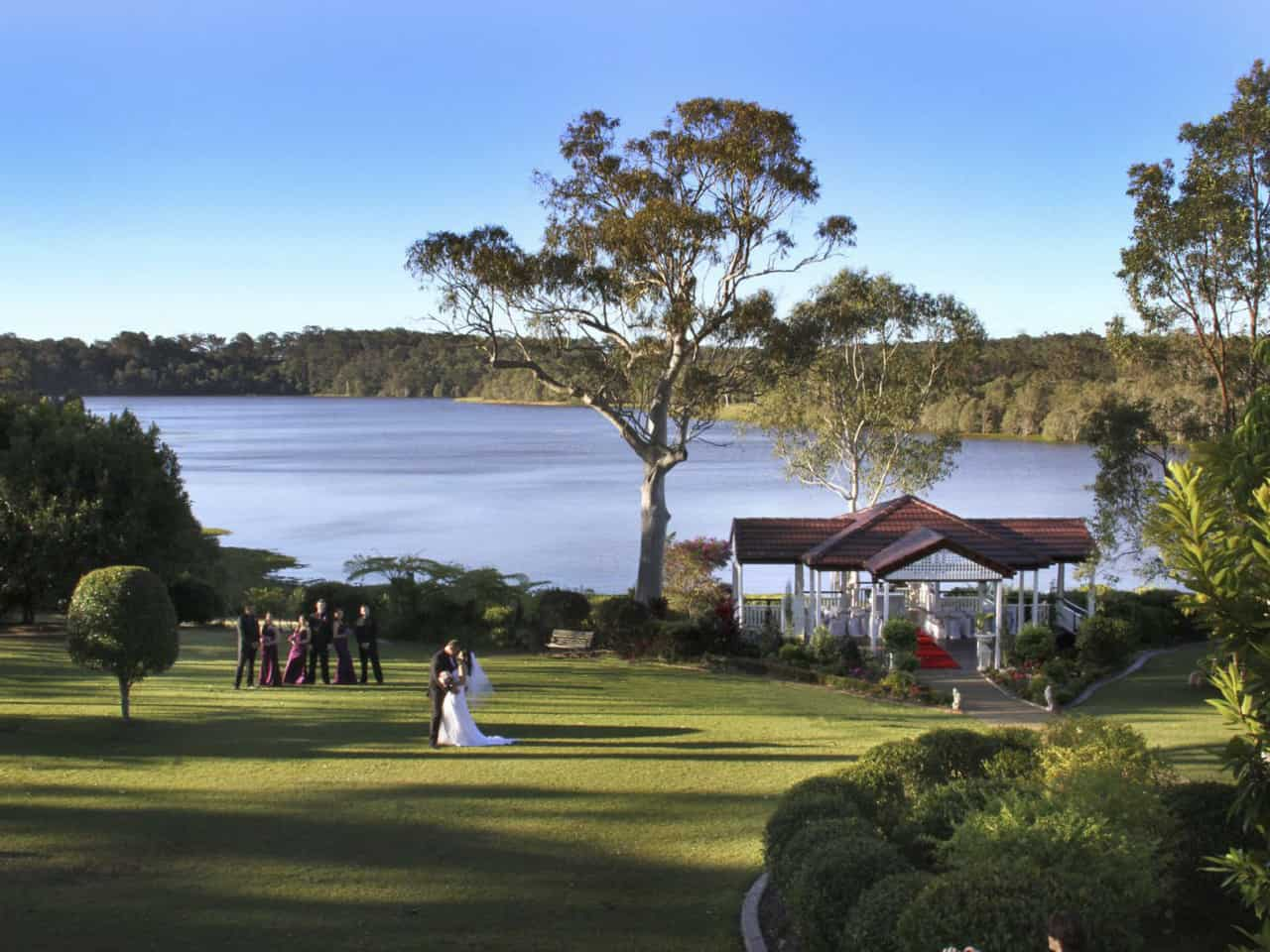 Lakeside wedding ceremony with bride and groom on lawn