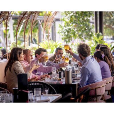 Gathering enjoying drinks on long table