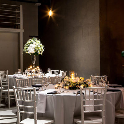 Warehouse space with round tables and subdued lighting