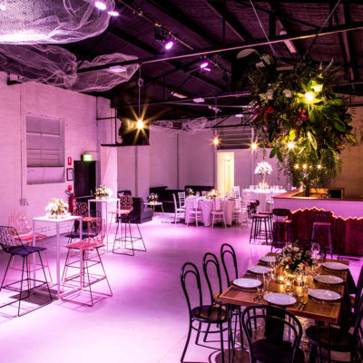 Warehouse space with long tables and pink lighting