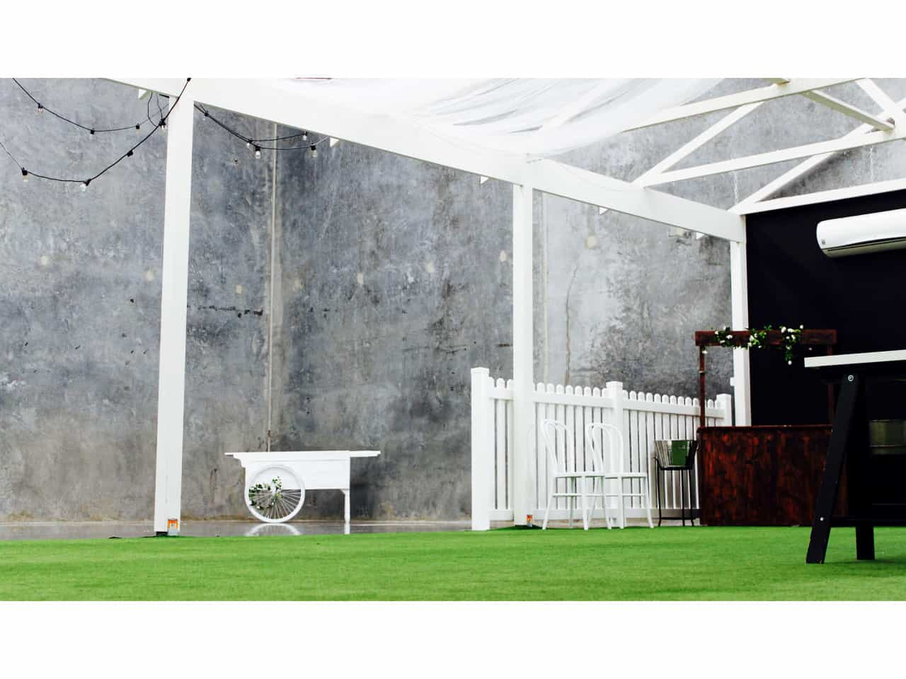 Open area function space with green lawn under marquee