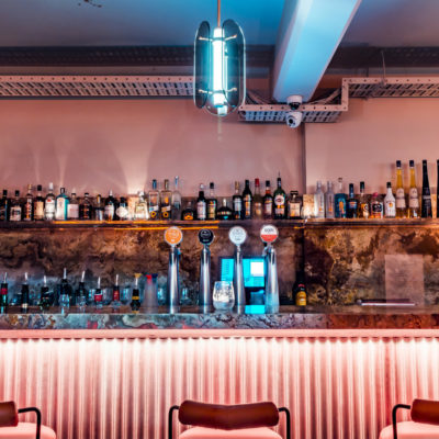 Bar area with shelves with bottles and neon lighting