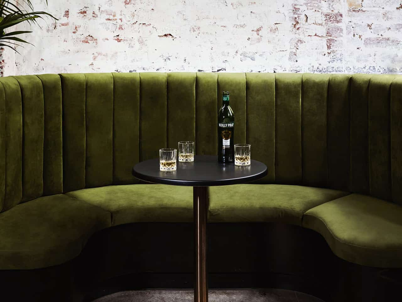 Green sofa with round table and whiskey bottle against brick white washed wall